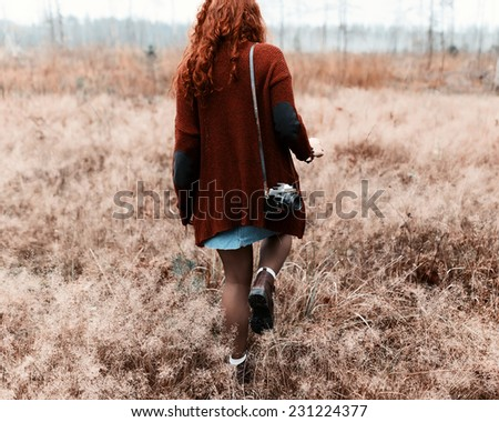 Fashion beautiful girl hipster goes to share with a camera on his shoulder