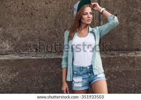 fashion beautiful girl posing near concrete wall
