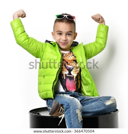 Fashion beautiful little boy in green winter clothing jacket sitting with hands up over white background - stock photo