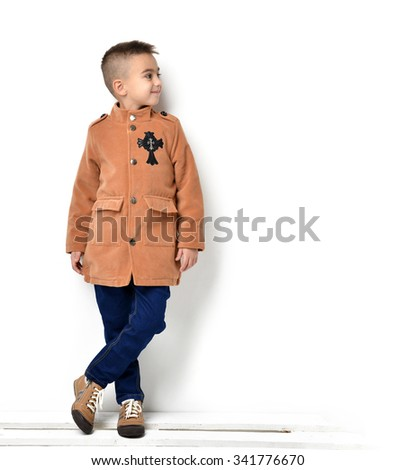 Fashion beautiful little boy in orange brown clothing jacket and jeans standing and looking right at the corner over white background - stock photo
