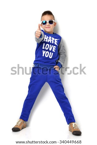 Fashion beautiful little boy in sunglasses blue cloth jeans standing and giving thumb up sign over white background - stock photo