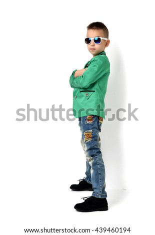 Fashion beautiful little boy in sunglasses blue cloth jeans standing and green jacket over white background - stock photo