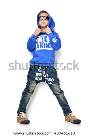 Fashion beautiful little boy kid in sunglasses blue hoodie cloth jeans standing looking up over white background - stock photo