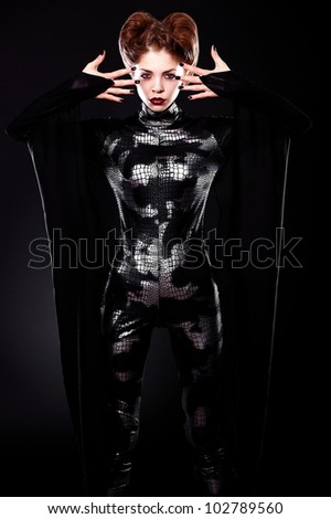 Fashion beautiful sexy vampire girl with hairstyle and makeup in vampire costume - stock photo