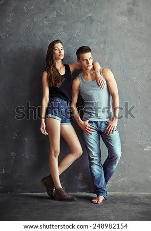 fashion beautiful young couple on grey wall background  - stock photo