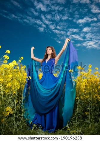 Fashion beautiful young woman in blue dress posing outdoor with cloudy dramatic sky in background. Attractive girl with elegant dress posing in canola field. Long hair brunette enjoying the rapeseed  - stock photo