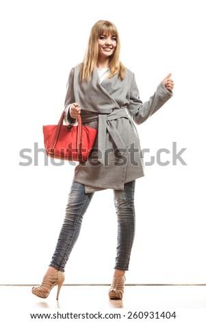Fashion beauty and elegance concept. Full body fashionably woman elegant gray belt coat holding red handbag isolated on white - stock photo