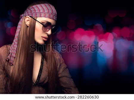Fashion Beauty. Beautiful Party Girl with Healthy Long Brown Straight Hair, Wearing Brown Dress, Bandanna and Sunglasses in Hippie Style. Close up Portrait on  Abstract Background with Copy Space. - stock photo