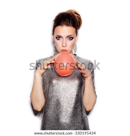 Fashion Beauty Girl blowing a red balloon. Woman Portrait. Stylish Haircut and Makeup. Vogue Style. On White background no isolated  - stock photo