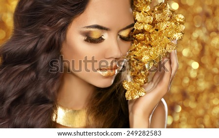 Fashion Beauty Girl Portrait. Eyes makeup. Golden jewelry. Attractive woman model with long brown hair over bokeh lights glitter background.