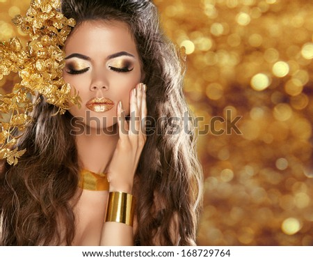 Fashion Beauty Girl Portrait Isolated on golden Christmas glittering lights Background. Glamour Makeup. Gold Jewelry. Hairstyle.