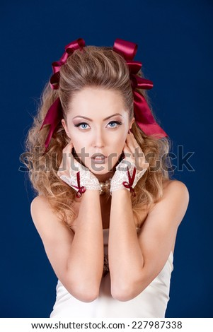 Fashion Beauty Girl. Portrait of Beautiful Woman Model in the Doll Style with Red Bow, Professional Hairstyle and Perfect Make up. Studio shot. Dark blue background. - stock photo