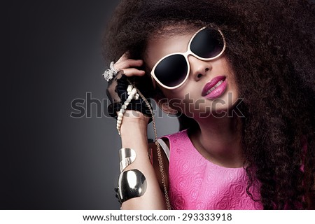 Fashion beauty girl posing in sunglasses. Sexy young woman holding jewelry. Girl with long healthy hair. - stock photo