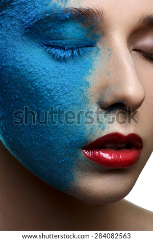 Fashion beauty girl with blue snow on face and red lips
