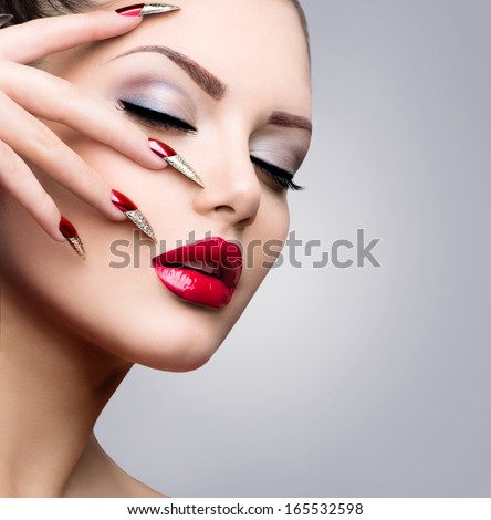 Fashion Beauty Model Girl. Manicure and Make-up. Nail art. Beautiful Woman With Red and Golden Nails and Luxury Makeup. Beautiful Girl Face and Hand  - stock photo