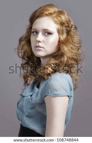 Fashion-beauty portrait of attractive young woman with red wavy curly hair,freckles,perfect make-up wearing trendy designer blouse,skirt on gray background - stock photo