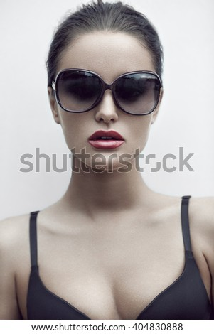 Fashion beauty portrait of beautiful glamorous brunette sexy woman in sunglasses and underwear. Professional makeup.