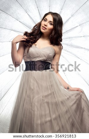 Fashion beauty portrait of gorgeous young woman with long curly hair in luxury evening dress