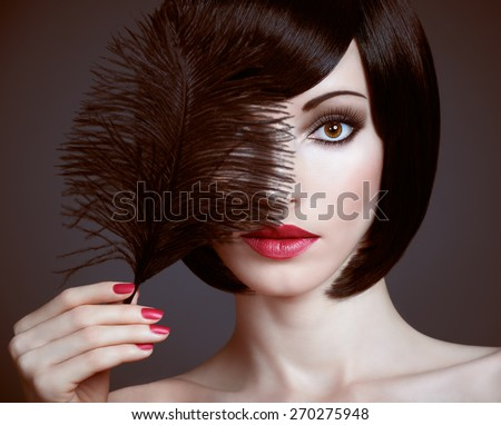 Fashion beauty portrait of nude brunette woman with silky bob hairstyle on dark. Sensual lady mysteriously looks, covering eye by black feather. Brown-eyed girl, luxury makeup, red lips. Face closeup - stock photo