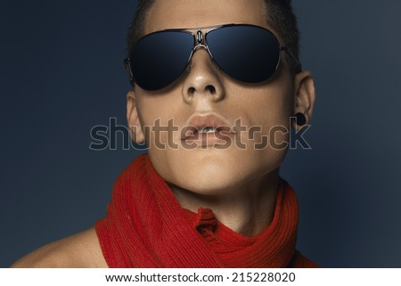 Fashion beauty portrait of teenager with sunglasses and scarf against blue background - stock photo