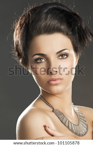 fashion beauty portrait of young pretty lady with hair style and an important old fashion silver necklace, she looks in to the lens, her arms are crossed and her hands are near the shoulders - stock photo