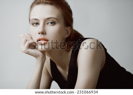 Fashion beauty portrait of young red-haired model with long straight hair in black dress. - stock photo
