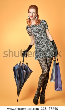 Fashion beauty sexy woman with shopping bags,umbrella,stylish accessories.Elegant luxury model redhead girl in lace stockings, glamor gloves.Unusual creative vogue party people.RetroVintage, copyspace