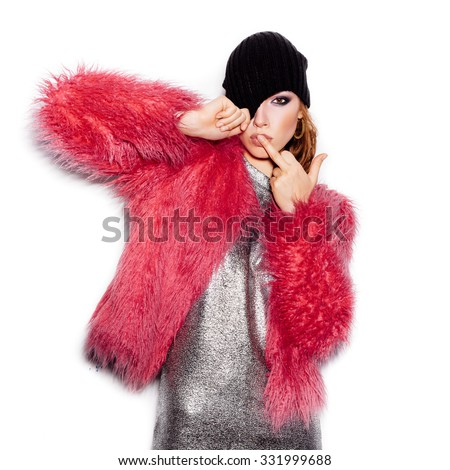 Fashion Beauty Swag Girl wearing silver dress, pink fur coat, black beanie hat. Stylish Haircut and Makeup. Gorgeous young Woman kissing middle finger on white background no isolated - stock photo
