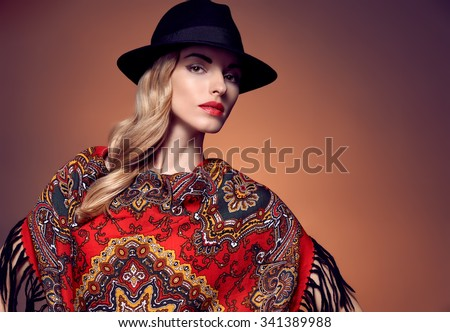 Fashion beauty woman in stylish hat and colored shawl. Autumn winter model blond girl with long blonde wavy hair in ethnic pattern headscarf. Unusual creative attractive people.Retro Vintage,copyspace - stock photo