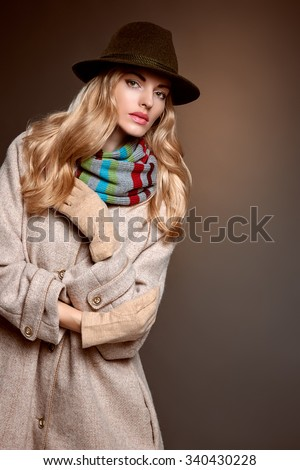 Fashion beauty woman in stylish long coat, hat. Autumn winter model blonde girl with long blonde wavy hair in colored striped scarf, gloves. Unusual creative attractive people. Retro Vintage,copyspace - stock photo