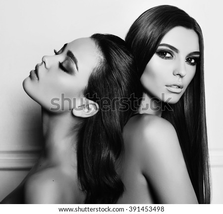 fashion black and white photo of two beautiful girls with dark hair and evening makeup, posing in studio - stock photo