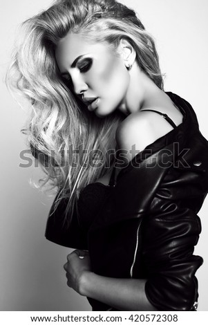 fashion black and white studio photo of gorgeous sexy woman with blond hair in lingerie and leather jacket