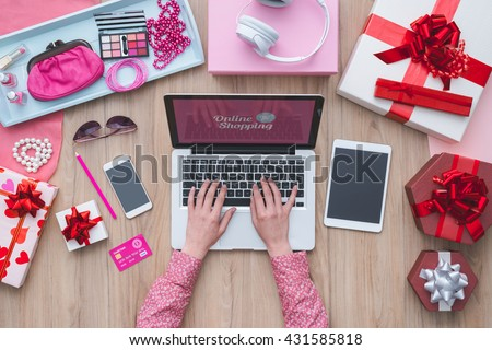 Fashion blogger working at office desk with a laptop: fashion, beauty and technology concept