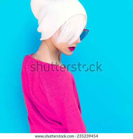 Fashion Blond model with trendy Cap and Sunglasses on a blue background - stock photo