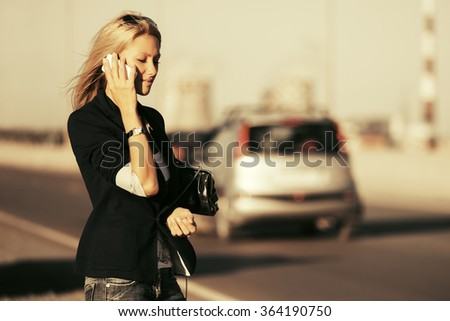 Fashion blond woman calling on the phone outdoor - stock photo