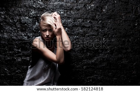 Fashion blond woman near black brick wall - stock photo