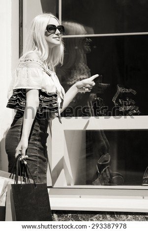 Fashion blond woman with shopping bags at the mall window - stock photo