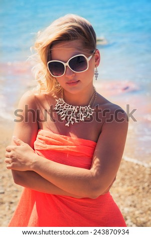 Fashion blonde female in vacation. Posing with cute summer style, pare on bikini, sunglasses and big white necklace - stock photo