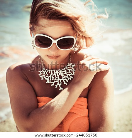 Fashion blonde female in vacation. Posing with cute summer style, pare on bikini, sunglasses and big white necklace. Photo with instagram style filters - stock photo