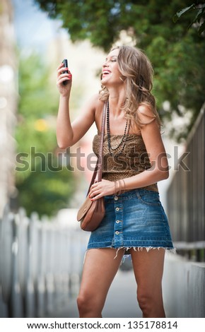 fashion blonde girl with short skirt at playing with mobile phone.Young attractive woman talking on a cell phone in a  street.happy young woman play by mobile phone on the street - stock photo