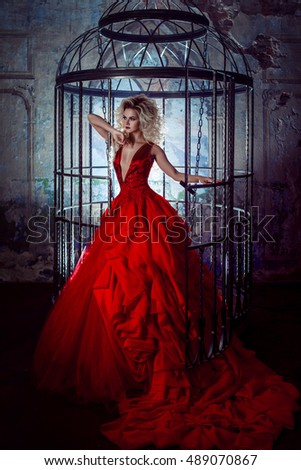 Fashion blonde in red dress with fluffy skirt near the birdcage, concept of liberation