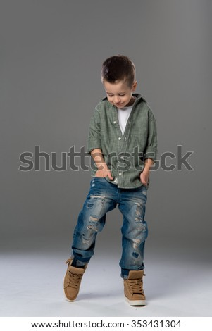 Fashion boy looking down on grey background  - stock photo