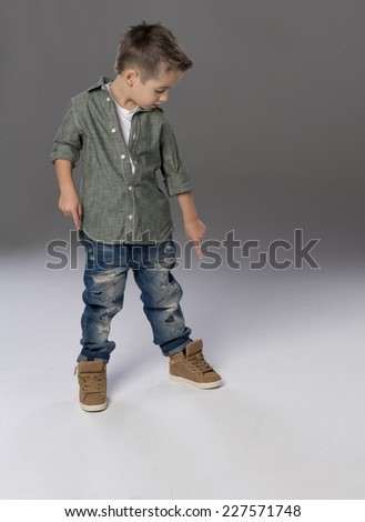 Fashion boy pointing down on grey background