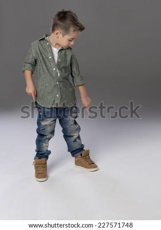 Fashion boy pointing down on grey background - stock photo