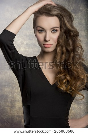 fashion brunette female posing with cute black dress, stylish make-up and long shiny wavy hair. Charming expression looking in camera  - stock photo