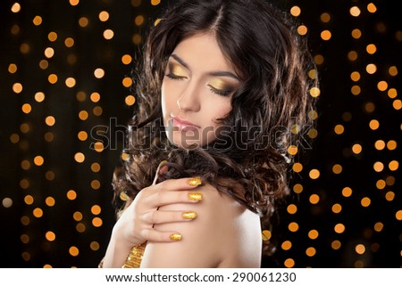 Fashion brunette girl with Long curly hair, beauty makeup, luxury jewelry. Beautiful attractive young woman in golden dress posing over holiday lights glitter background. - stock photo