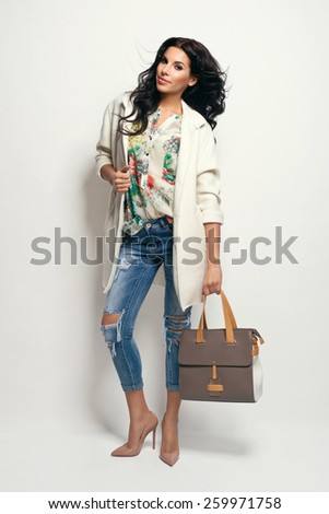 Fashion brunette model in nice clothes posing in the studio. Wearing coat, handbag, ripped jeans - stock photo