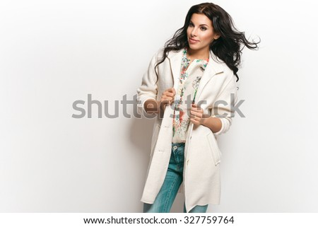 Fashion brunette model in nice clothes posing in the studio. Wearing coat, handbag, ripped jeans and white boots - stock photo