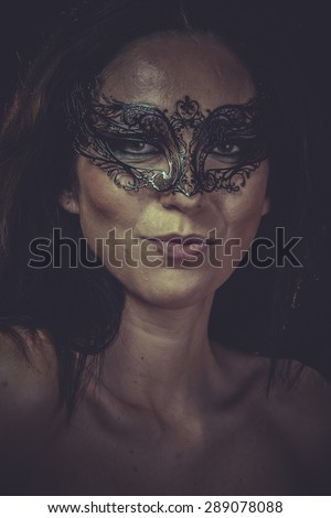 Fashion brunette woman in black mask metal frills - stock photo
