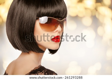 Fashion brunette woman in sunglasses. Black bob hairstyle. Red lips makeup. Glamour girl posing over holiday background. - stock photo